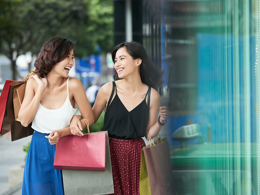 Laughing happy Asian women enjoying shopping in big city