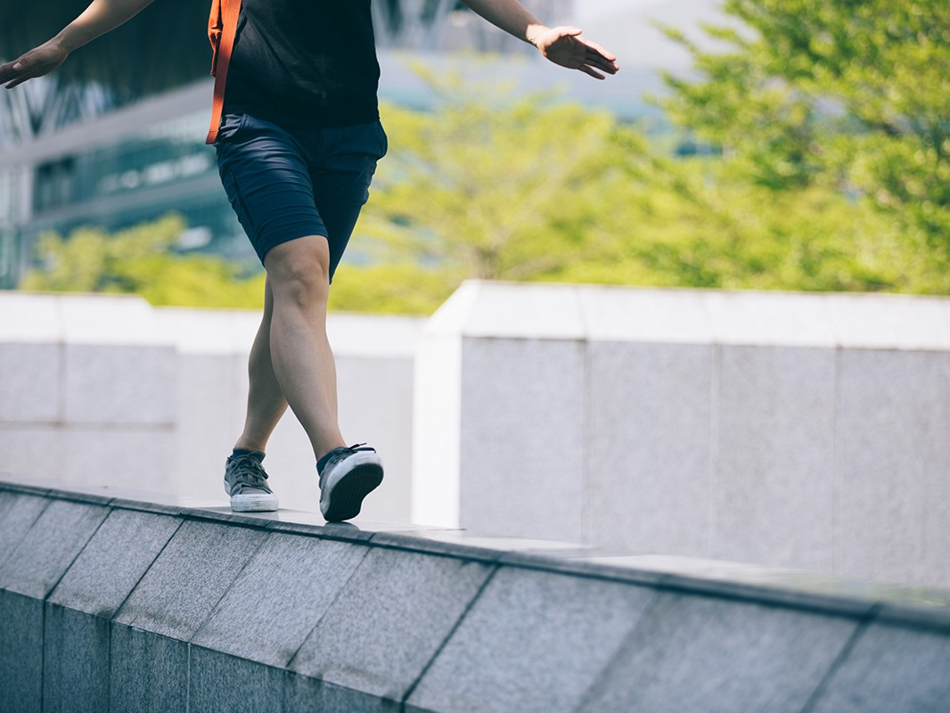 Woman walking on the edge of a urban building wall at city