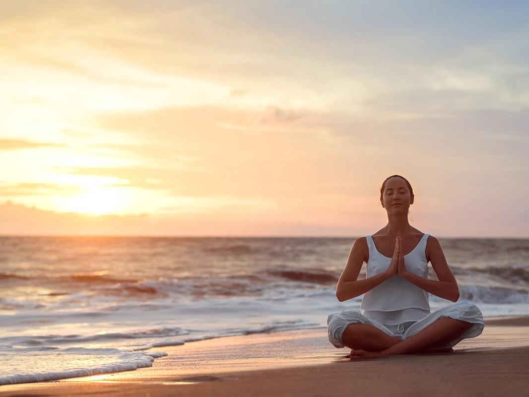 Young girl doing yoga at sunset