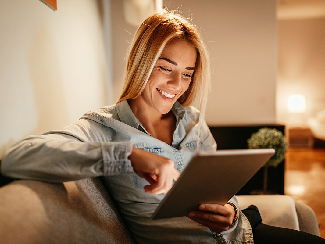Attractive young woman holding a tablet at home